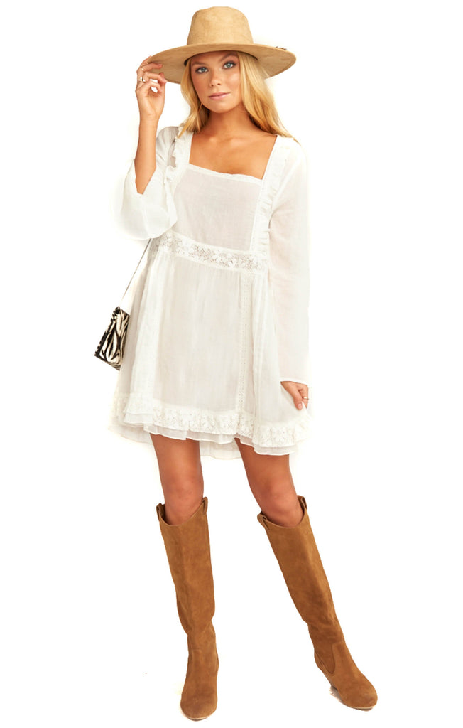 blonde model in white mini dress large brim hat and over the knee bots