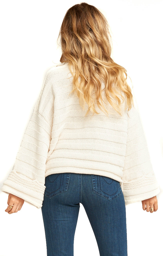 back of cream knit pullover with bell sleeves and denim pants