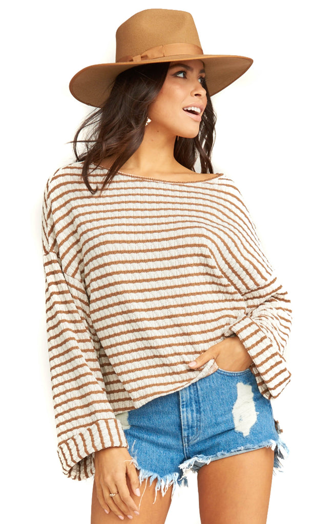 model in striped white and caramel pullover with bell sleeves and hand in denim shorts