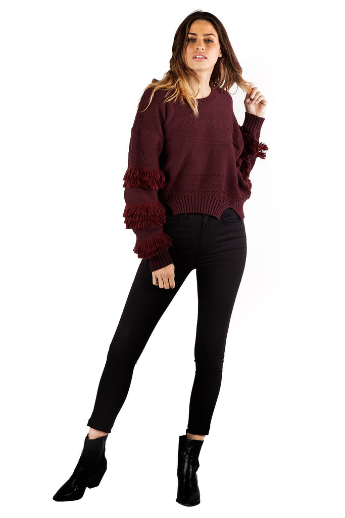 pullover port sweater with fringe details and black pants