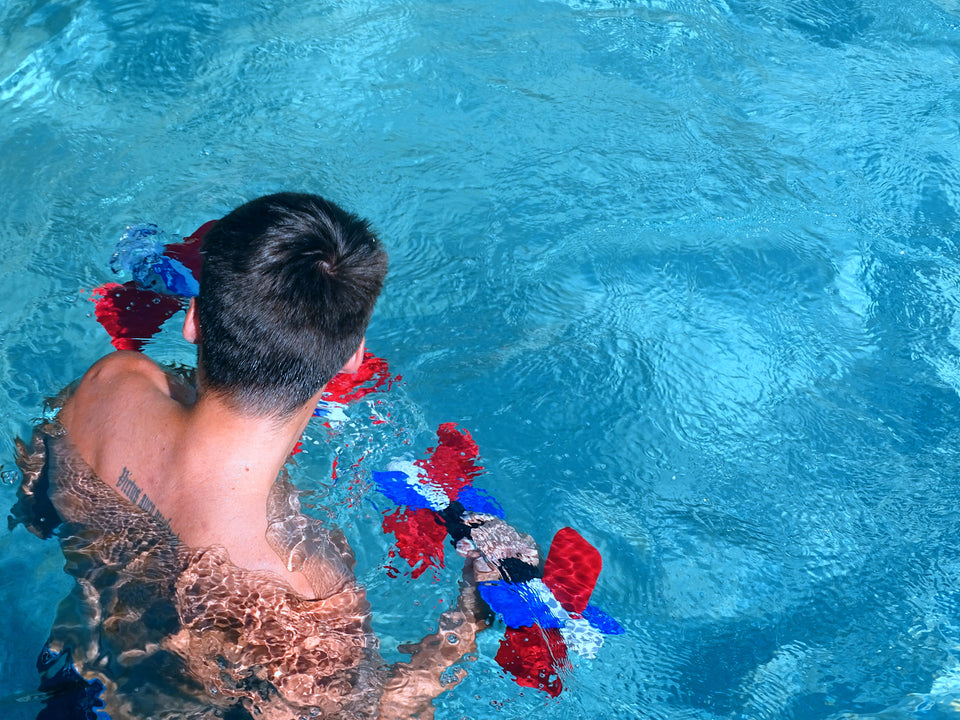 young man doing bicep curls with Aqua Bladez in pool