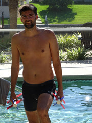 Young man walking out of pool while smiling, holding aqua bladez set