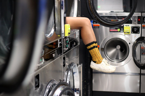 mustard socks girl legs laundrette laundromat photography hot gold knit socks unique byron bay nsw australia style lifestyle mannie brand socks colourful socks