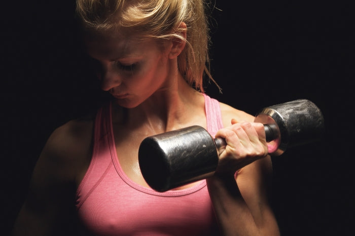Woman building muscle with dumbbell