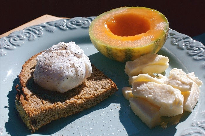 Poached egg on toast breakfast with melon
