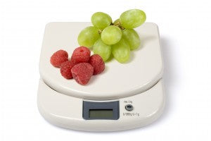 Weighing raspberries and grapes on a scale