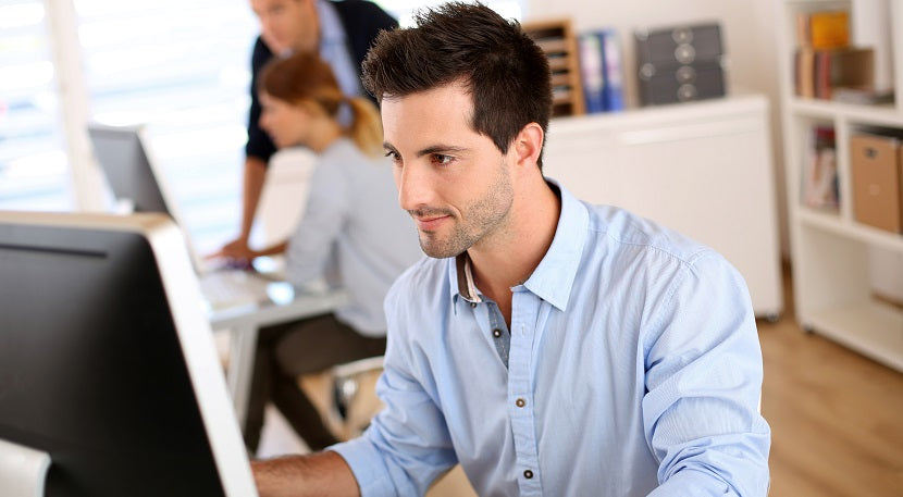 Office worker sitting on desk smiling