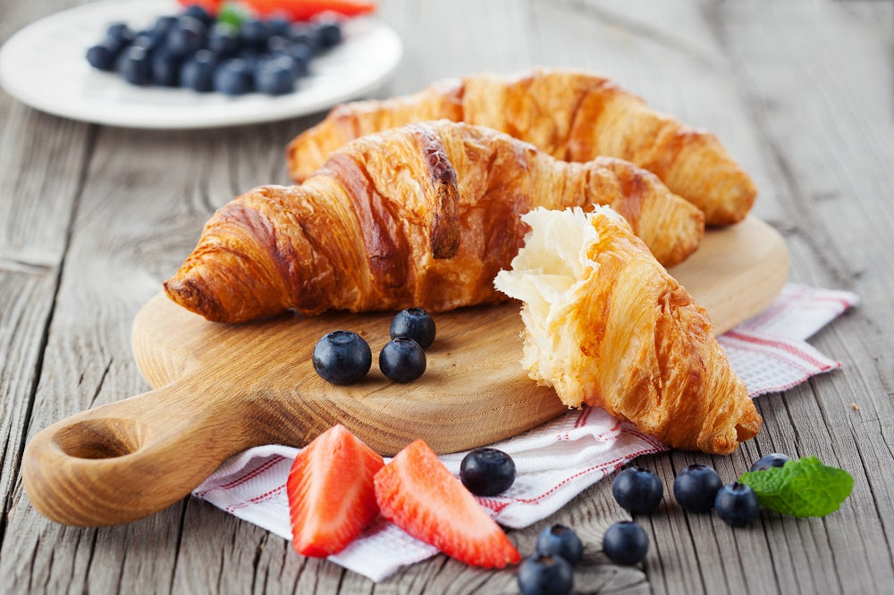 Delicious croissant snack with berries, strawberries and blackberries