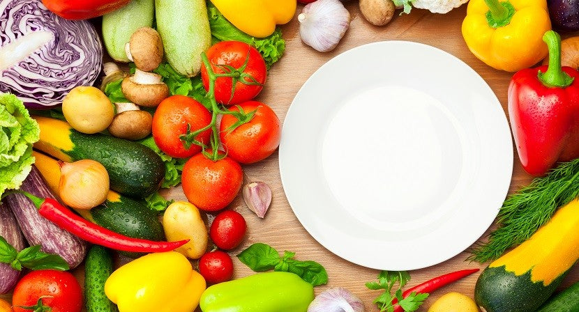 Empty plate surrounded by loads of vegetables