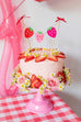 pink cake stand with strawberry cake banner