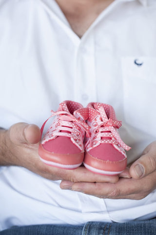 Baby shoes in father's hands