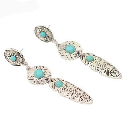 Native American post earrings with turquoise resin and engraved metal.