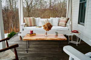 Live edge, slab top coffee table being used on a covered porch. Sustainably, handmade by Knaughty Log Company in the USA.