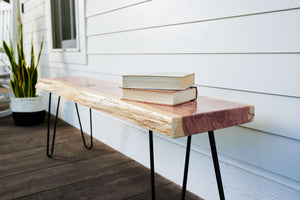 Raw edge slab top bench with hairpin legs used on covered porch, handmade by Knaughty Log Company in the USA.