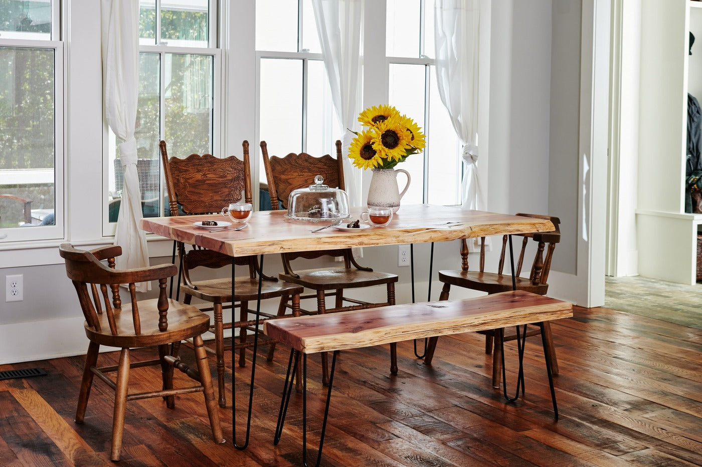 Live edge dining table in kitchen with a matching bench and 4 chairs to seat 6 people. Sustainably handmade in the USA by Knaughty Log Co.