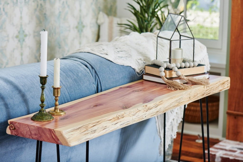 Live edge sofa table behind blue couch. One solid wood slab with hairpin legs, handmade by Knaughty Log Co in the USA.