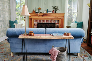 Raw edge slab top sofa table sitting behind a blue couch in front of a fireplace. Handmade by Knaughty Log Co.
