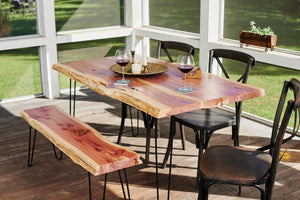 Live edge outdoor dining table sitting in covered sunroom with a matching slab top bench.