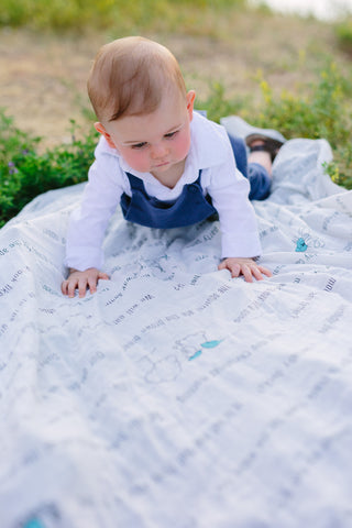 baby boy looking at a sight words swaddle blanket