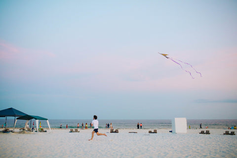 man running with a kite at the beach