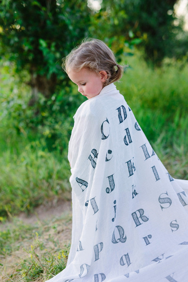 little girl with alphabet swaddle blanket