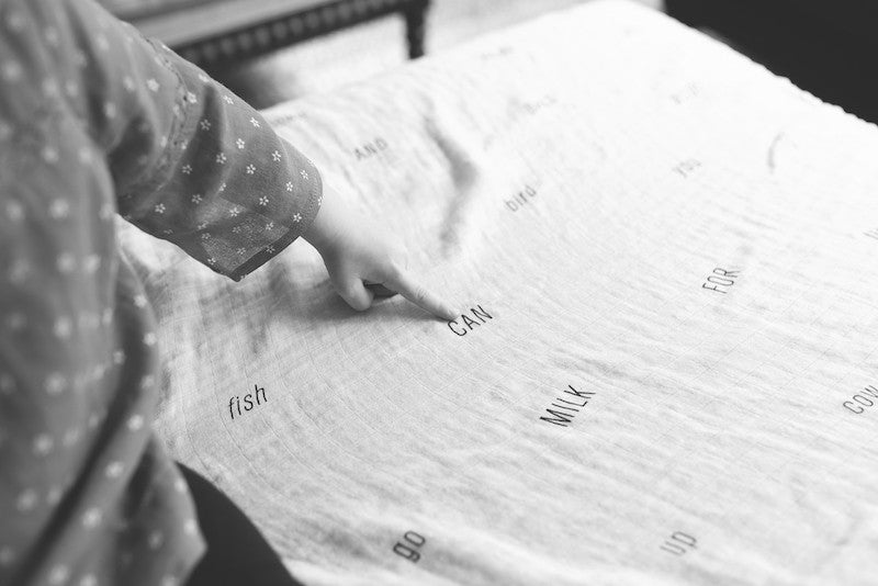 girl pointing to sight word on bamboo cotton swaddle blanket