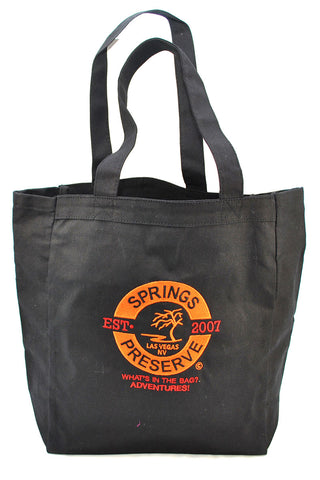 "Black tote bag with orange Springs Preserve logo featuring ""est. 2007"" text."