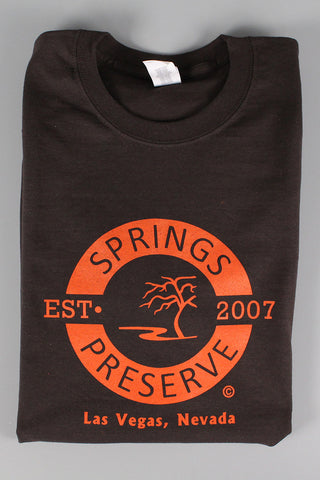 "Folded brown t-shirt with orange ""Springs Preserve Est. 2007"" logo"