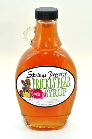 Glass jar of orange colored syrup with Springs Preserve Prickly Pear Syrup label