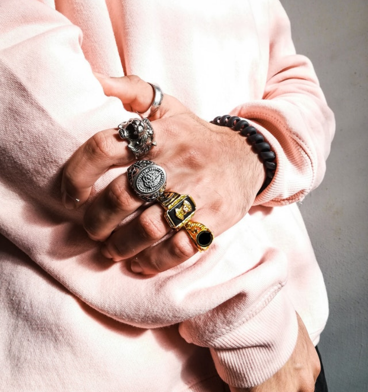 A man idly waiting at the same time showing his five rings on his fingers