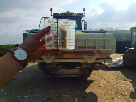 spreader with emma foot holding up the shaker used to calibrate the fertiliser