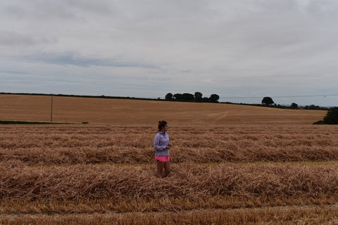 female farmer stood in straw fields on farmland