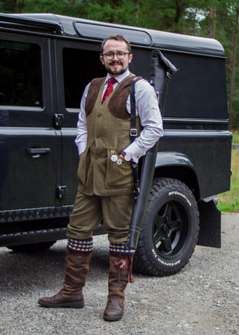Man wearing shooting clothing stood next to landrover 4x4