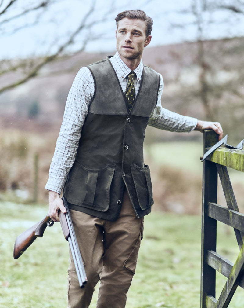 Man opening a gate wearing Lightweight Shooting Waistcoat by Musto