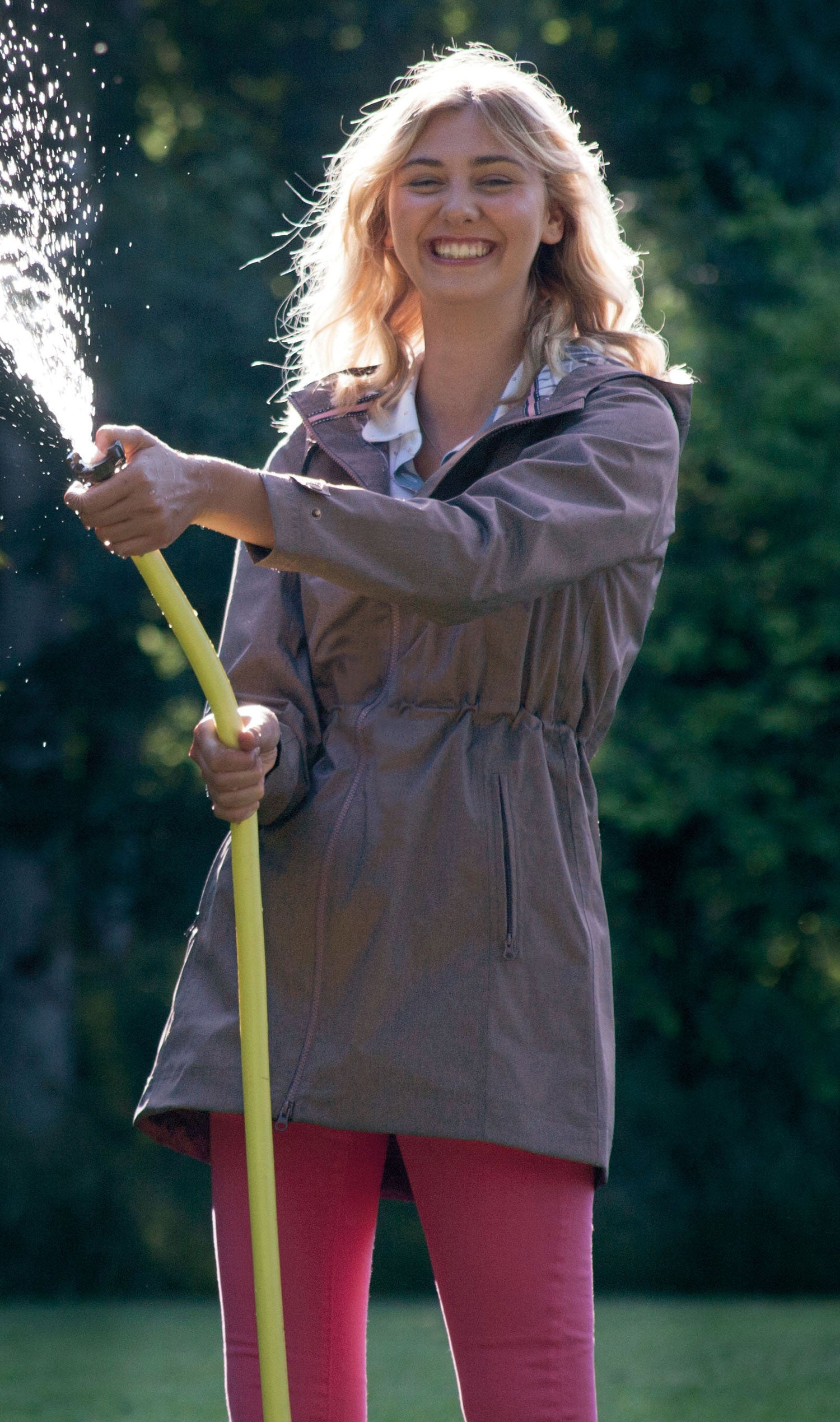 lady spraying water through a hose in a jake murphy coat