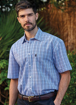 Man wears blue Poole Mini Check Shirt by Champion