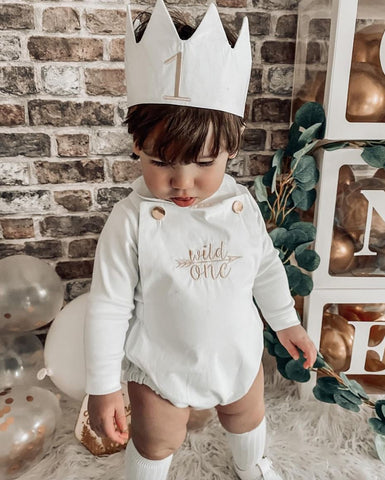 "Baby wearing a ""wild one"" romper and crown during a virtual birthday celebration"