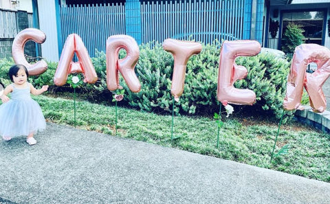 "Toddler girl wearing a dress outside in front of birthday balloons that spell ""Carter"" during drive-by first birthday party"