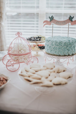 Cinderella-themed toddler birthday party table with a pumpkin carriage centerpiece and pale blue birthday cake.