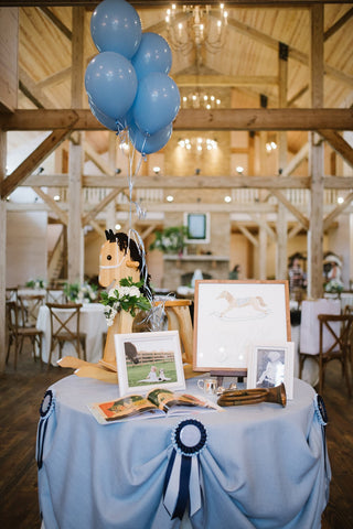 Styled table with rocking horse and images for a derby-themed 2nd birthday party.