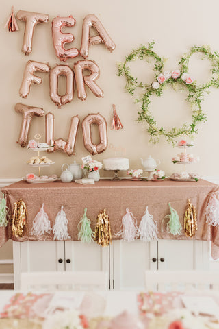 Tea-party-themed 2nd birthday party featuring a pastel-colored cookie, tea, and cake display.