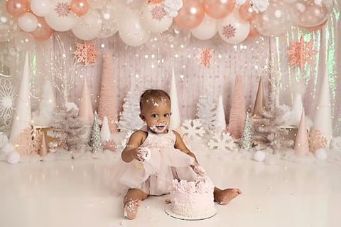 Baby girl sitting in front of a birthday backdrop with a pink smash cake in front of her