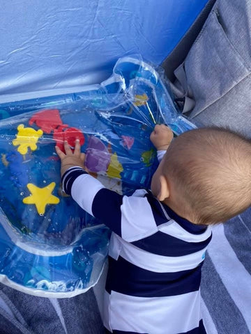 A baby does tummy time on a sensory play mat