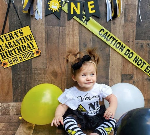 "Baby girl sitting in front of a yellow ""Vera's Quarantine Birthday"" sign and yellow, white, and black balloons"