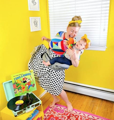 Mother holding 1-year-old baby as she dances to a Mickey Mouse record in a bright yellow room