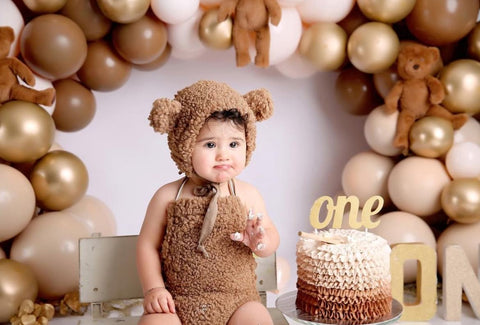 Baby dressed as a bear next to a brown and white smash cake.