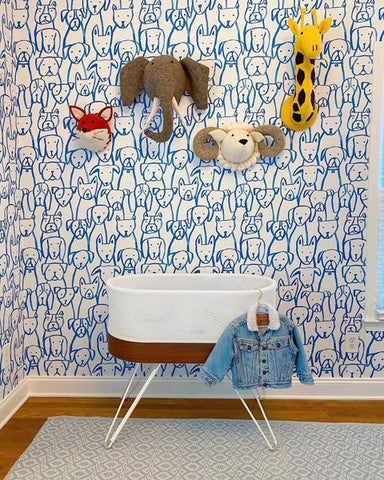 A SNOO bassinet in front of nursery wallpaper printed with a blue hand-drawn-looking pattern of dogs. Above the SNOO there are a plush felt giraffe, elephant, ram, and fox on the wall.