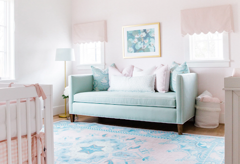 A pale pink baby nursery with a light blue couch and light blue-patterned rug.