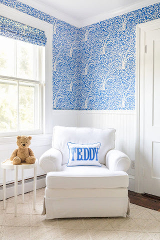 A blue baby nursery with a blue leaf-print wallpaper and matching leaf-print window shades.