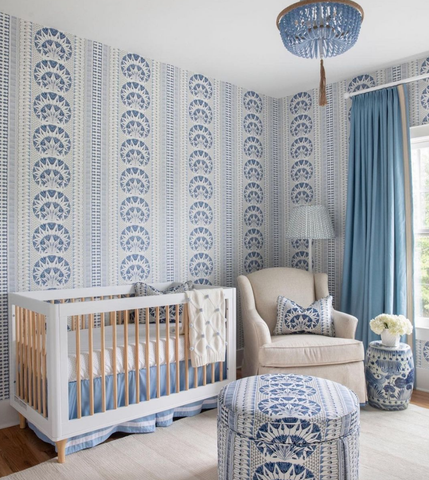 A baby nursery with a bold blue-and-white print wallpaper—the same pattern appears on a pillow and ottoman in the room.